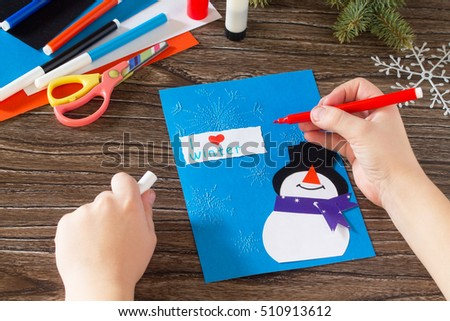 Child paper glued parts that I love winter. The child makes a greeting card with a snowman. Made with his own hands. Children's art project, a craft for children. Craft for kids. #510913612