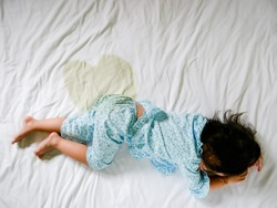 Child pee on a mattress, Little girl feet and pee in bed sheet, Child development concept , selected focus.