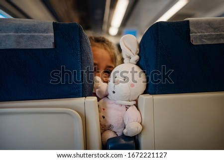 Child peeking between seats.Child sitting in front seat.Children on plane/bus/train rides.Children in transportation. Annoying kid.Airplane child passenger,traveling with kids.Bringing toys to trips