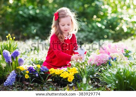Child planting spring flowers in sunny garden. Little girl gardener plants hyacinth, daffodil, snowdrop in flower bed. Gardening tools and water can for kids. Family with children work in the backyard