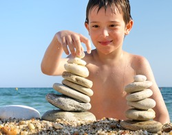 child played on the beach with stones