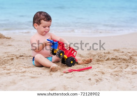 Child playing a red car on the beach - stock photo