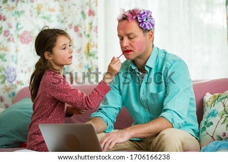 Child playing and disturbing father working remotely from home. Little girl applying makeup. Man sitting on couch with laptop. Family spending time together indoors.