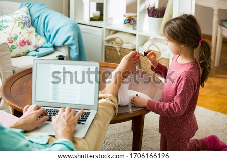 Child playing and disturbing father working remotely from home. Little girl applying nail polish on toenails. Man sitting on couch with laptop. Family spending time together indoors.