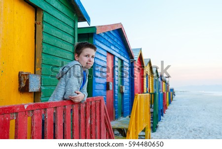 Child playing at famous colorful huts of Muizenberg beach near Cape Town in South Africa