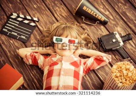 Child playing at home. Kid with vintage cinema objects. Entertainment concept. Top view stock photo