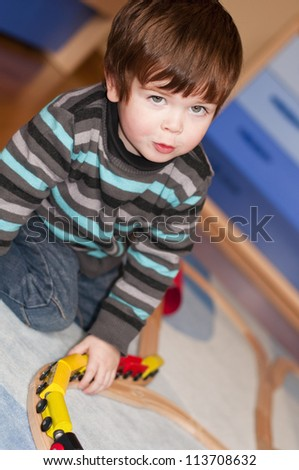 Child playing at kindergarten with a toy train