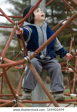 Child playing at playground on a climbing rope frame.