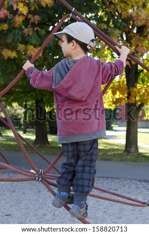 Child playing at playground on a rope climbing frame.