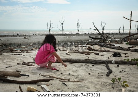 child playing at the polluted beach