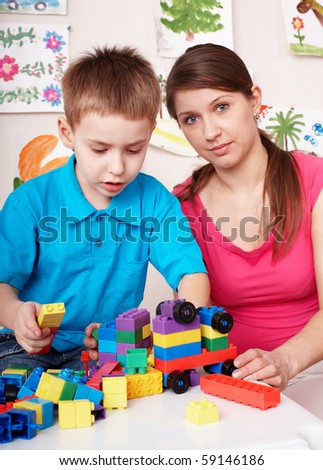 Child playing construction set in games room. Preschool.