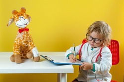 Child playing doctor with toy animal giraffe. Happy smiling kid boy at home or daycare. Pediatrician for preschool and kindergarten kids. Pediatric, healthcare and people concept. School for pediatric