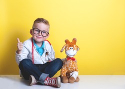 Child playing doctor with toy animal giraffe. Happy smiling kid boy with thumb up at home or daycare. Pediatrician for preschool and kindergarten kids. Pediatric, healthcare and people concept.