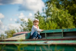 child playing in a boat on the riverbank, selective focus