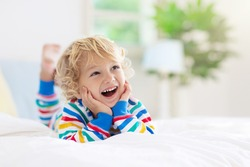 Child playing in bed in white sunny bedroom with window. Kids room and interior design. Baby boy at home. Bedding and textile for children nursery. Kid with toy and book. Nap and sleep time.