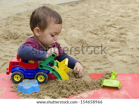 Child playing in sandpit with toy truck car or digger.