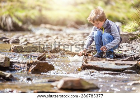 Child playing in summer sunshine with a paper boat in stream