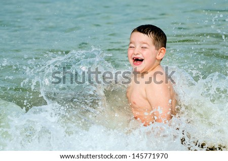 stock-photo-child-playing-in-surf-at-beach-145771970.jpg
