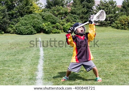 Child playing lacrosse screams for joy while holding stick over head