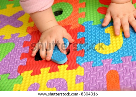 child playing multi colored alphabet puzzle