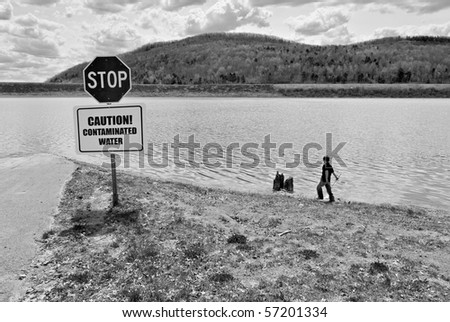 Child Playing near Polluted Lake - stock photo