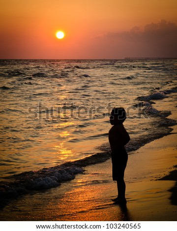 Child playing on beach at sunset