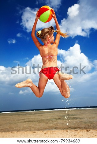 Child  playing on  beach with ball.