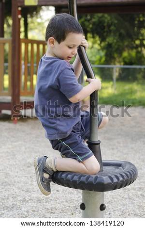 Child playing on modern playground equipment. - stock photo