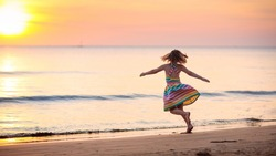 Child playing on ocean beach. Kid jumping in the waves at sunset. Sea vacation for family with kids. Little girl in beautiful dress running on tropical beach of exotic island during summer holiday.