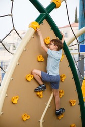 child playing on Outdoor children playground in a city park. Boy In Adventure Park having fun in high wire park. Male toddler on climbing wall. Boy on children playground in summer day. Sport for kids