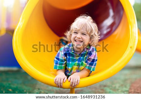 Photo of  Child playing on outdoor playground. Kids play on school or kindergarten yard. Active kid on colorful slide and swing. Healthy summer activity for children. Little boy climbing outdoors.