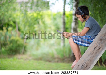 Child playing on the computer with headphones outdoor