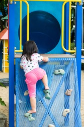 child playing on the playground, climbing on the  wall