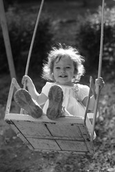 Child playing on the swings - black and white photo with yellow filter effect, shallow depth of field, back lighting