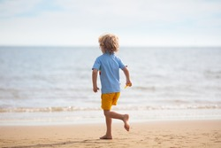 Child playing on tropical beach. Little boy with bucket and spade at sea shore. Family summer vacation. Kid building sandcastle. Water and sand fun for children. Kids play, build castle on ocean coast