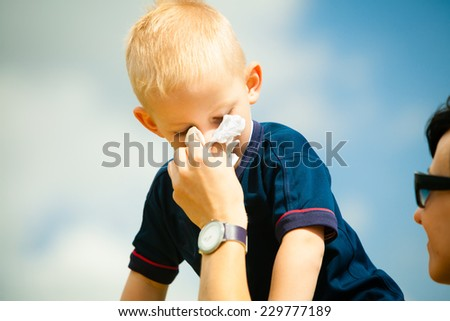 Child playing outdoor and blowing nose in handkerchief. Little boy kid sneezing in tissue. Catarrh or allergy to pollen symptom.