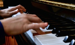 Child playing piano. Close up side view of blurred fast moving young hands and fingers playing a song on the keys of an upright shiny black piano.
