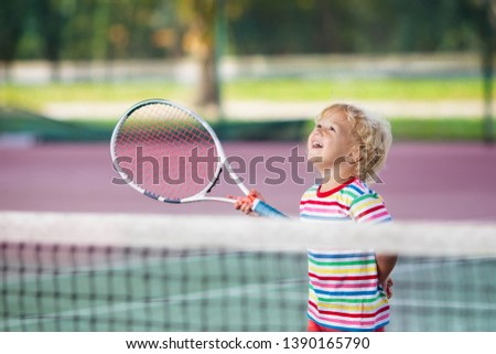 Child playing tennis on indoor court. Little boy with tennis racket and ball in sport club. Active exercise for kids. Summer activities for children. Training for young kid. Child learning to play. #1390165790
