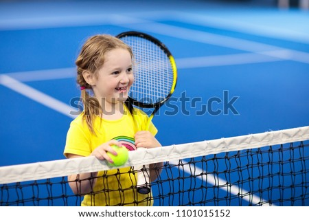 Child playing tennis on indoor court. Little girl with tennis racket and ball in sport club. Active exercise for kids. Summer activities for children. Training for young kid. Child learning to play. Stock photo ©