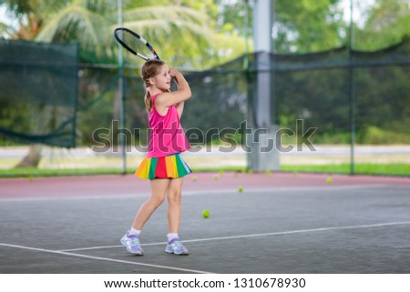 Child playing tennis on indoor court. Little girl with tennis racket and ball in sport club. Active exercise for kids. Summer activities for children. Training for young kid. Child learning to play. #1310678930