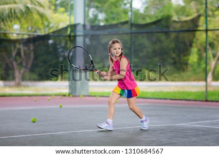 Child playing tennis on indoor court. Little girl with tennis racket and ball in sport club. Active exercise for kids. Summer activities for children. Training for young kid. Child learning to play. #1310684567