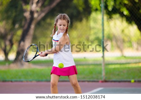 Child playing tennis on indoor court. Little girl with tennis racket and ball in sport club. Active exercise for kids. Summer activities for children. Training for young kid. Child learning to play. #1512038174