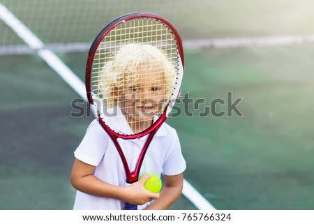 Child playing tennis on outdoor court. Little boy with tennis racket and ball in sport club. Active exercise for kids. Summer activities for children. Training for young kid. Child learning to play. #765766324