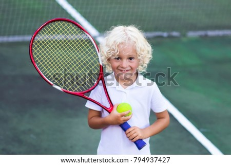 Child playing tennis on outdoor court. Little boy with tennis racket and ball in sport club. Active exercise for kids. Summer activities for children. Training for young kid. Child learning to play. #794937427