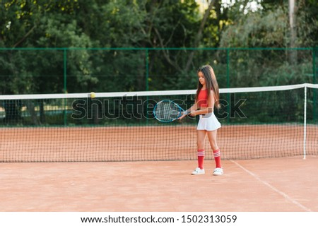 Child playing tennis on outdoor court. Little girl with tennis racket and ball in sport club. Active exercise for kids. Summer activities for children. Training for young kid. Child learning to play