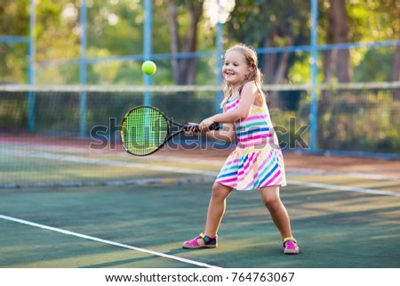 Child playing tennis on outdoor court. Little girl with tennis racket and ball in sport club. Active exercise for kids. Summer activities for children. Training for young kid. Child learning to play. #764763067