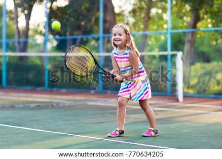 Child playing tennis on outdoor court. Little girl with tennis racket and ball in sport club. Active exercise for kids. Summer activities for children. Training for young kid. Child learning to play. #770634205