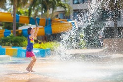 Child playing under tip bucket in water park. Kids play with splash dump bucket. Family fun in amusement center on hot summer day. Sun protection for children. Water slides for kid.