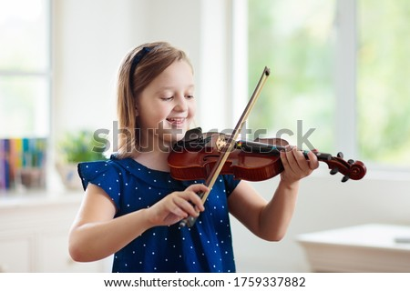 Child playing violin. Remote learning from home. Arts for kid. Little girl with musical instrument. Video chat conference lesson. Online music tuition. Creative children play song. Classical education Сток-фото ©