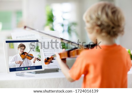 Child playing violin. Remote learning from home. Arts for kids. Little boy with musical instrument. Video chat conference lesson. Online music tuition. Creative children play song. Classical education ストックフォト ©